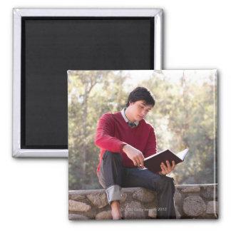 Libro y sentada de lectura del estudiante en la pa imán cuadrado