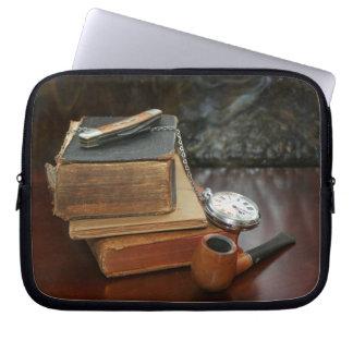 Libros, tubo, reloj de bolsillo y cuchillo en la t fundas computadoras