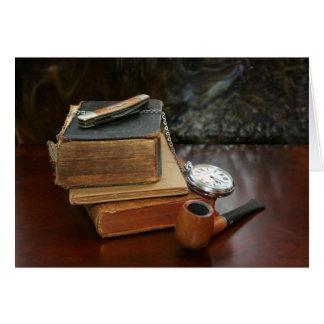 Libros, tubo, reloj de bolsillo y todavía del cuch tarjeta de felicitación