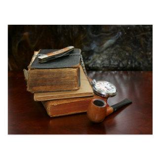 Libros, tubo, reloj de bolsillo y todavía del cuch tarjetas postales