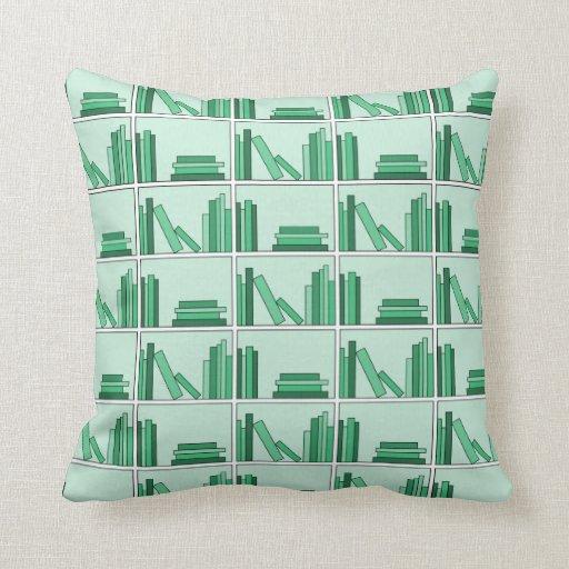 Libros verdes en estante cojines
