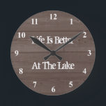 """Life is better at the lake wood grain wall clock<br><div class=""""desc"""">Life is better at the lake wood grain print wall clock. Vintage typography template for funny quote or saying. Rustic decorations for new home, house, hunting cabin, store, shop, business etc Brown barn wooden panel background design with dial numbers. Cute retirement gift idea for retired men and women. Country chic...</div>"""