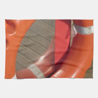 Lifebuoy anaranjado en el embarcadero de madera en toallas