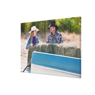 Lifting bales of hay canvas print