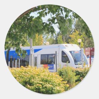 Light rail train seen through landscape. round stickers