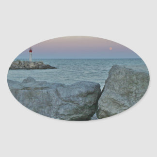 Lighthouse on the Rocky Shore Oval Sticker