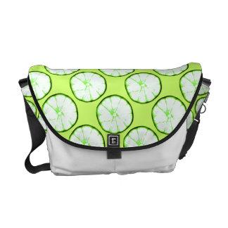 lime slices on vibrant green background messenger bag