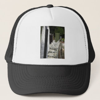 Line of closed beach chairs and umbrellas trucker hat