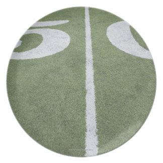 Línea de yardas cincuenta en campo de deportes platos