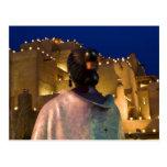 Linternas que encienden el edificio del adobe, con postal