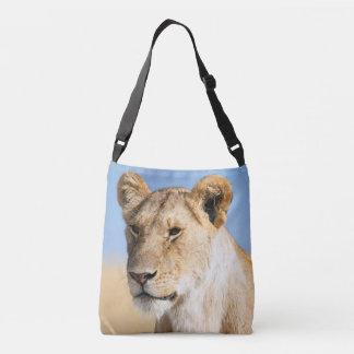 Lioness against blue sky crossbody bag