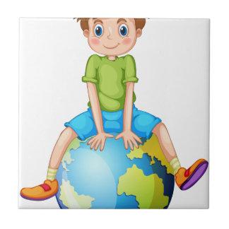 Little boy sitting on blue planet tile