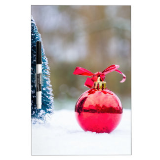Little christmas tree and red bauble in snow dry erase board