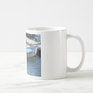 Little fishing boats anchored in a village port coffee mug