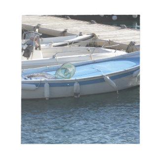 Little fishing boats anchored in a village port notepad