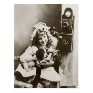 Little girl and puppy playing with telephone postcard