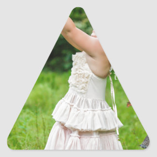 Little Girl Catching a Butterly Triangle Sticker
