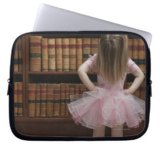 little girl in tutu reading book covers in computer sleeve