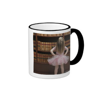 little girl in tutu reading book covers in coffee mugs