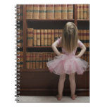 little girl in tutu reading book covers in notebook