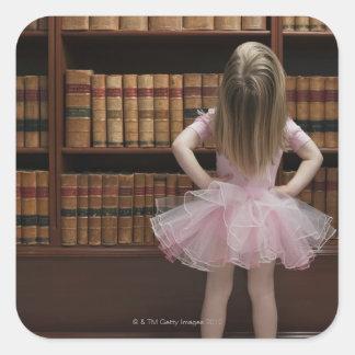 little girl in tutu reading book covers in square sticker