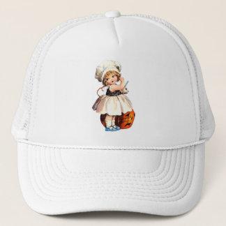 little girl with pumpkin trucker hat