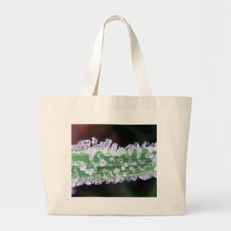 Little ice cubes (frost) on green grass canvas bag