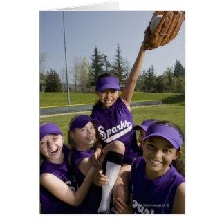 Little league players carrying teammate greeting card