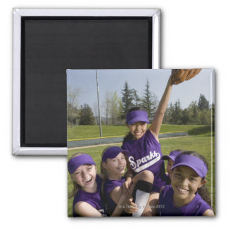 Little league players carrying teammate magnet
