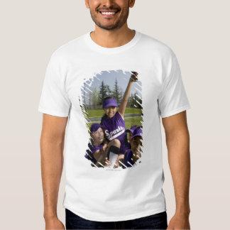 Little league players carrying teammate t-shirt