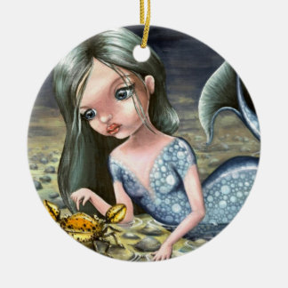 Little mermaid playing with a crab christmas tree ornament