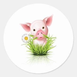 Little pink pig in grass round sticker