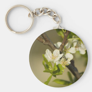 Little white flowers on a branch with green leafs keychain