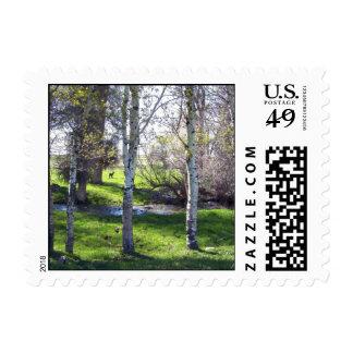 Llama a través de árboles timbre postal
