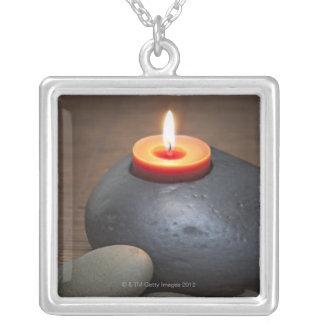 Llama de vela ardiente con las rocas en tranquilo collar plateado