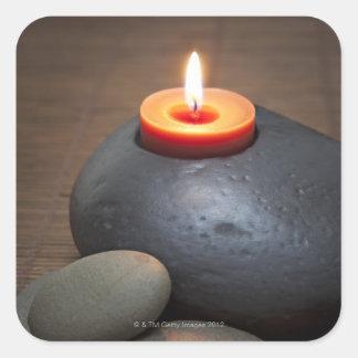 Llama de vela ardiente con las rocas en tranquilo pegatina cuadrada