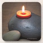 Llama de vela ardiente con las rocas en tranquilo posavasos