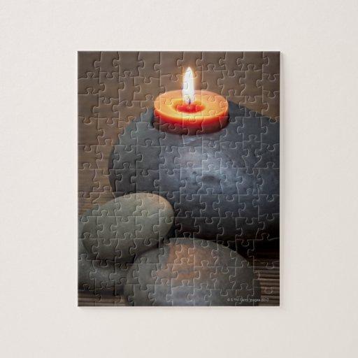 Llama de vela ardiente con las rocas en tranquilo puzzle