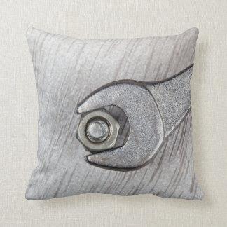 Llave, perno y nuez en superficie de metal cojín decorativo