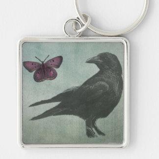 Llavero del premio negro del cuervo y de la maripo