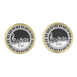 Llaves circulares del piano y notas embarulladas gemelos dorados