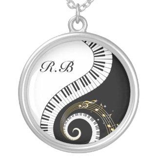 Llaves del piano del monograma y notas musicales collar
