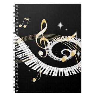 Llaves del piano y notas de oro de la música libreta espiral