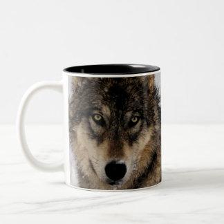 Lobo gris o lobo de madera que pone en la nieve taza de dos tonos