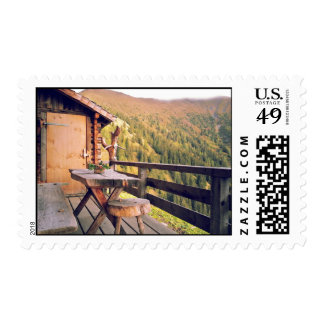 Log cabin with wooden table in mountains stamps