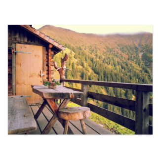 Log cabin with wooden table in mountains postcard