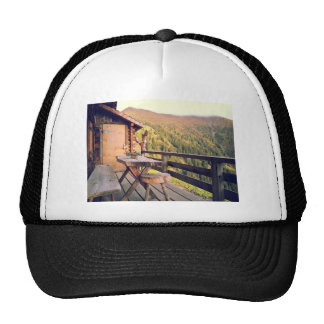 Log cabin with wooden table in mountains trucker hat