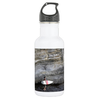 Lone surfer on tropical lava coast water bottle