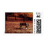 lonely bench in the autumn park postage
