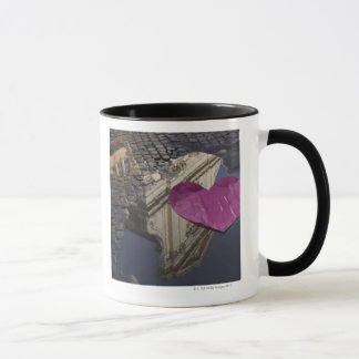 Lonely paper heart floating in a puddle. mug